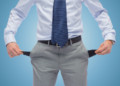 business, people, bankruptcy and failure concept - close up of businessman showing empty pockets over blue background
