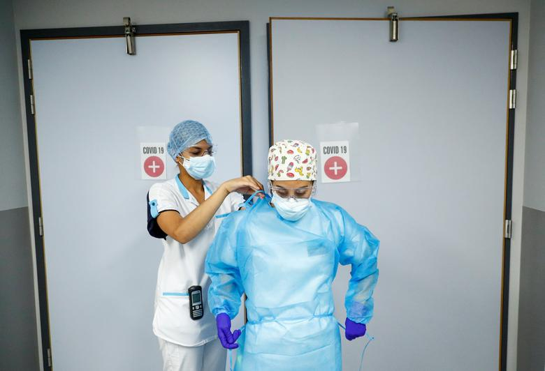 A nurse adjusts the protective suit of her colleague at the coronavirus treatment unit of a hospital in Brussels, Belgium September 18, 2020. REUTERS/Francois Lenoir